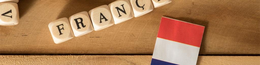 Native Speaker Französisch buchen bei Stimmenkartei - Französisch mit einzelnen Holzbuchstaben buchstabiert